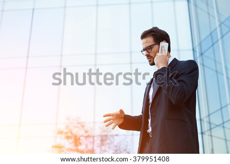 Successful financier decides affairs with partner via mobile phone while standing outside of his company's building, skilled male manager having emotional cell telephone conversation near skyscraper - stock photo