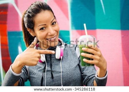 Successful fitness urban woman taking a rest for drinking and recommending detox smoothie. Healthy nutrition and lifestyle concept. - stock photo