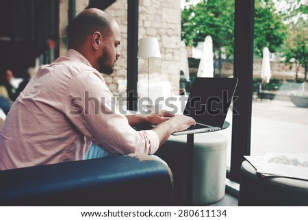 Successful freelancer man busy work on his laptop computer while sitting in modern coffee shop or hotel interior, young businessman using notebook in cafe or office hall, make money on-line,e-business - stock photo