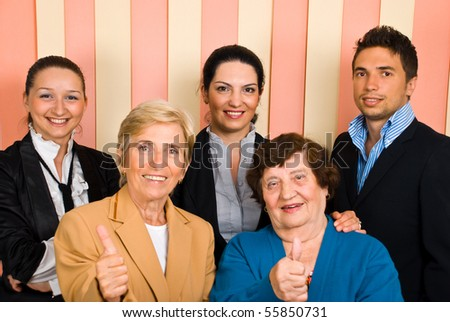 Successful group of five people with elderly in front giving thumbs up - stock photo