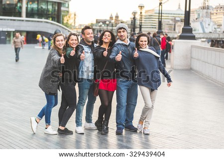 Successful group of friends showing thumbs upin London. They are four women and two men in their twenties, they are standing in a row, all very close by each other. Friendship and lifestyle concepts. - stock photo