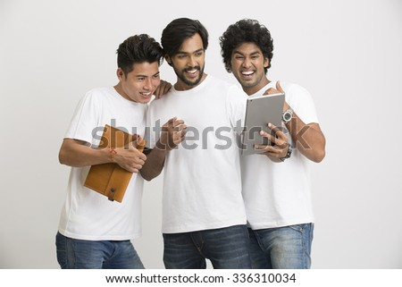 Successful group of Indian university friends using Pc tablet on white. - stock photo