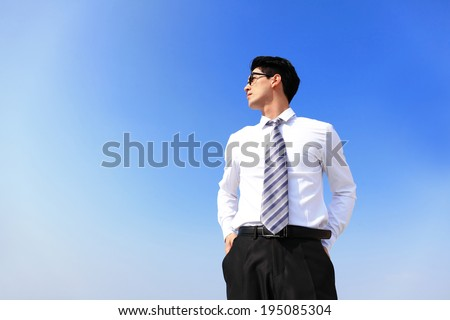 Successful handsome business man purposefully looking away with blue sky