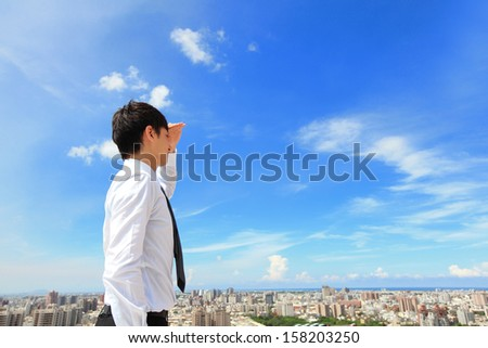 Successful handsome business man purposefully looking away with blue sky and city background, mode is a asian male - stock photo