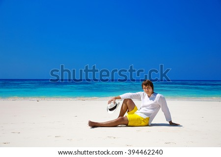Successful handsome man in hat resting on exotic seashore with blue water and white sand. Summer beach. Relax. Vacation Travel. Bliss freedom concept.  - stock photo