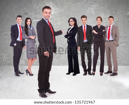 Successful happy business team being presented by a young leader, on gray background. young business man welcoming you to his business team