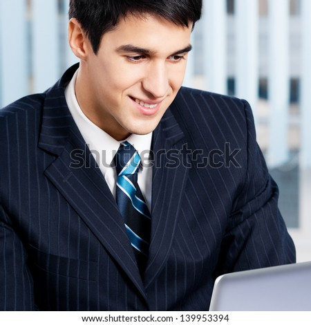 Successful happy smiling businessman working with laptop at office
