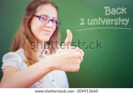 Successful happy young teacher or student at university or school classroom near a blackboard and show a thumbs up gesture. Concept of back to university. Selective focus on the hand - stock photo