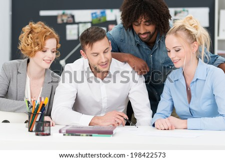 Successful hardworking young diverse business team working on a project together grouped around paperwork on the desk