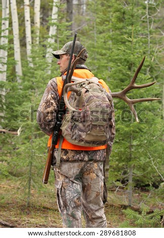 successful hunter walking in woods - stock photo