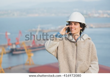 successful independent engineer smiling woman on industrial harbor with safety helmet talking on the phone. Pioneer woman at work. - stock photo