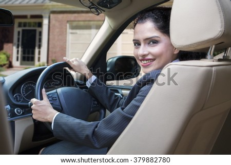 Successful indian businesswoman driving new car and smiling at the camera - stock photo
