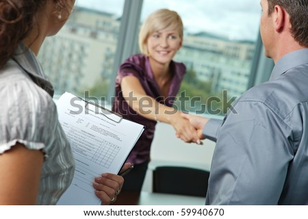 Successful job interview - happy employee shaking hands, smiling. Focus places on questionnarie in front, reults are excellent. - stock photo
