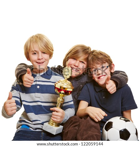 Successful kids with trophy and soccer ball holding their thumbs up - stock photo
