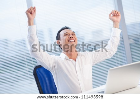 Successful leader with hands raised sitting at office - stock photo