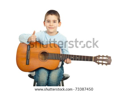 Successful little guitarist sitting on chair holding guitar and giving thumbs over white background