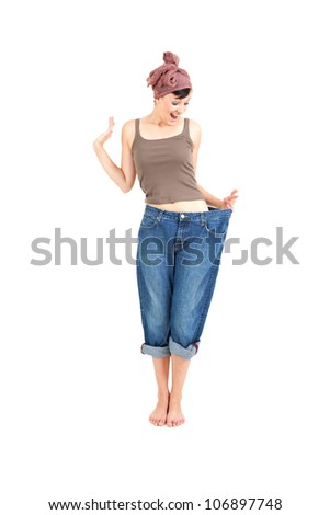 successful losing weight - woman in big trausers, full length, white background - stock photo