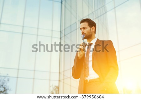 Successful luxury businessman put glasses to his lips and looking on copy space while standing outdoors, skilled male entrepreneur thinking about something serious after meeting with important clients - stock photo
