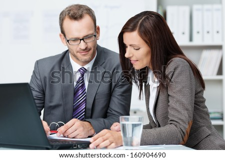 Successful male and female business partners having a discussion seated at a desk in the office together analysing some paperwork - stock photo