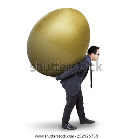 Successful male entrepreneur carrying a golden egg as his profit, isolated on white background