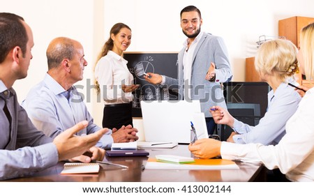 successful male expert makes a presentation at a meeting in the office - stock photo