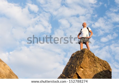 Successful male hiker standing on the mountain top enjoying the view in a warm day of summer