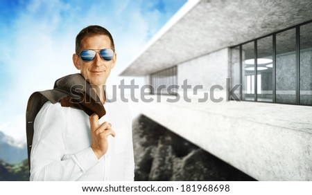 Successful man and his contemporary luxury house in mountains - stock photo