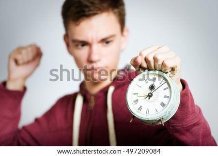 successful man angry at the alarm clock, isolated close-up