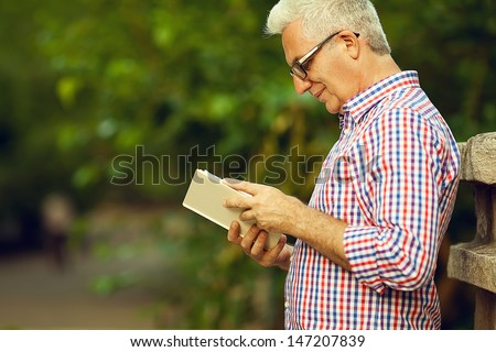 Successful man concept. Profile portrait of a smiling happy mature (old) man in trendy casual shirt & glasses reading book in the park. Sunny summer day. Copy-space. Outdoor shot