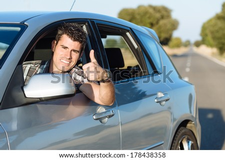 Successful man driving car and doing thumbs up. Cheerful male driver approving. - stock photo