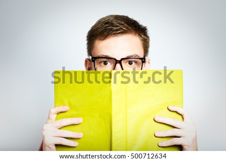 successful man hiding behind a book isolated on a gray background