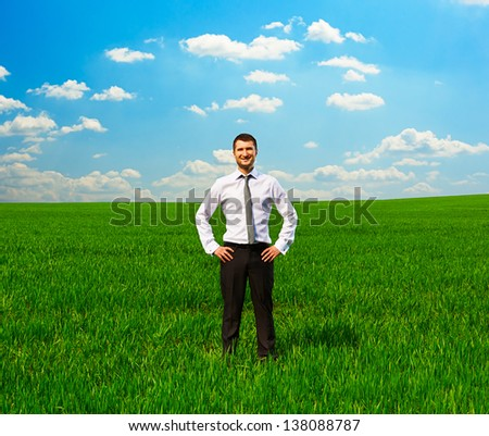 successful man in formal wear standing on green grass and smiling