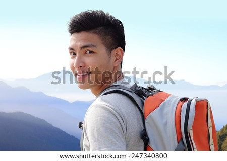 Successful man mountain hiker with backpack on the top of mountains. asian - stock photo