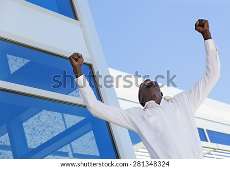 Successful man raising hands showing his business success - stock photo