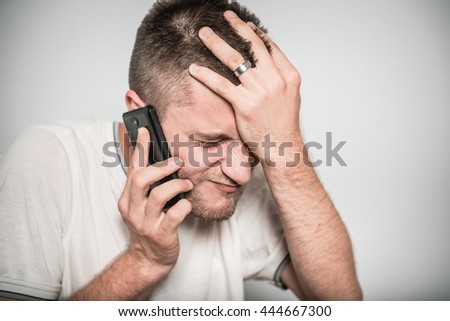 successful man upset talking on the phone isolated on a gray background - stock photo