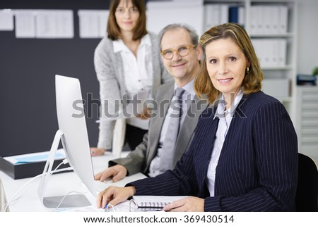 Successful management team with a middle-aged businessman and two women working together at a computer, focus to an attractive woman in the foreground