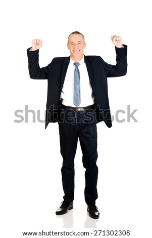 Successful mature businessman celebrating with arms up. - stock photo