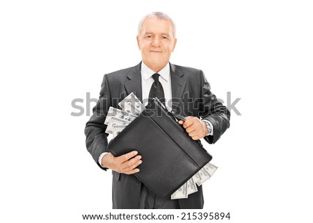 Successful mature businessman holding briefcase full of money isolated on white background - stock photo