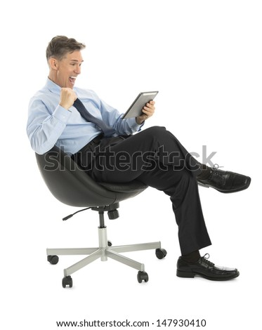 Successful mature businessman looking at digital tablet while sitting on office chair against white background