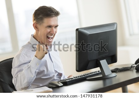 Successful mature businessman using Desktop PC in office - stock photo