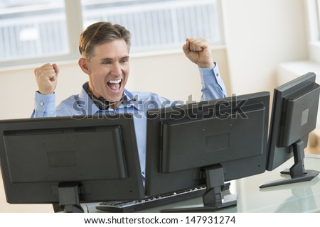Successful mature male trader screaming while using multiple computers at desk in office - stock photo