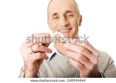 Successful mature man with broken cigarette. - stock photo