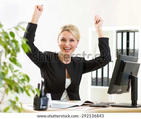 Successful middle-aged business woman with arms up sitting at pc in office