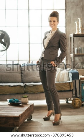 Successful modern business woman freshen up before work in her perfect loft apartment. Portrait of stylish smiling businesswoman in business suit