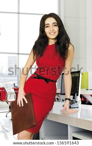 Successful modern business woman wearing red suit in the office