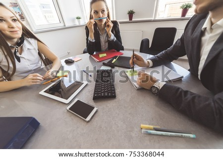 successful modern guy and girls are sitting at the table in the office, working together on a project