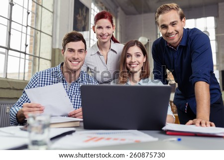 Successful motivated group of diverse young business people grouped around a laptop computer in the office smiling at the camera - stock photo