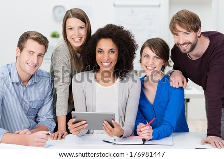 Successful motivated multiethnic business team posing grouped around an attractive African American woman looking at the camera with beaming friendly smiles