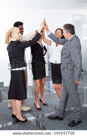 Successful Multiracial Business People Celebrating With A High-five - stock photo