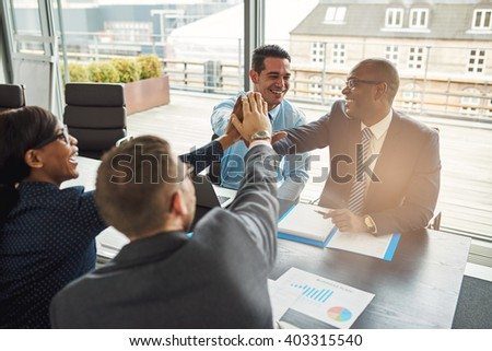 Successful multiracial business team seated at a table in an urban office cheering and congratulating each other after an outstanding achievement - stock photo